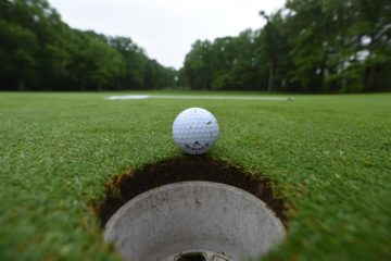 Golf Ball on Green next to hole
