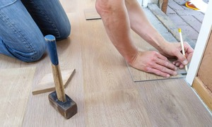 man marks new flooring in preparation for installation